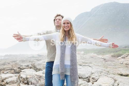 Casual couple stretching hands out on rocky landscape