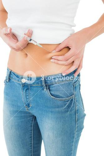 Closeup mid section of a woman injecting her belly