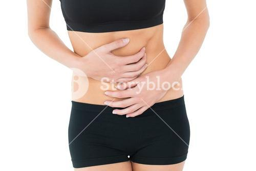 Mid section of a fit young woman with stomach pain