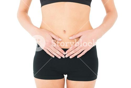 Closeup mid section of a fit woman with stomach pain