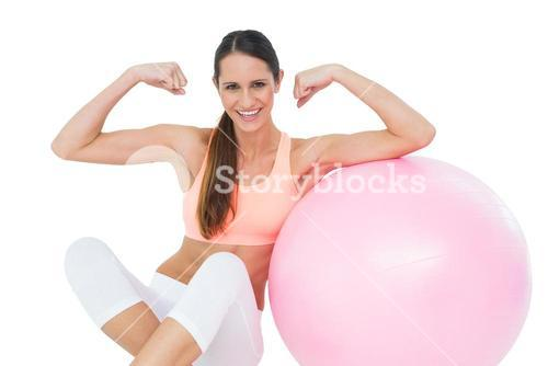 Cheerful fit woman flexing muscles by fitness ball