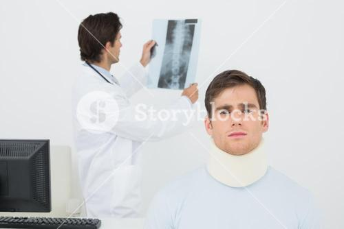 Patient in surgical collar with doctor examining spine xray behind