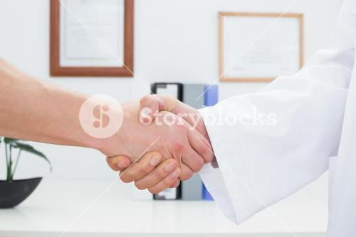 Closeup of a doctor and patient shaking hands