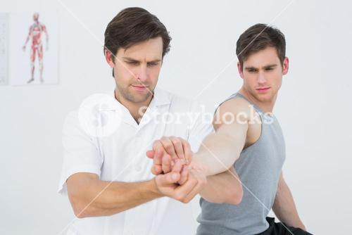 Male physiotherapist examining a young mans hand
