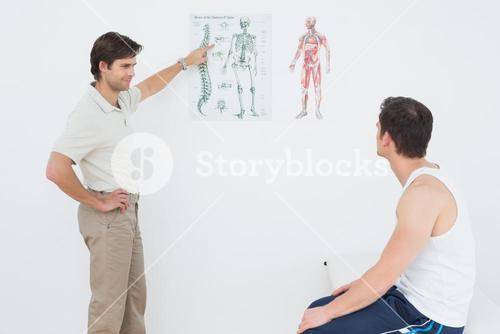 Physiotherapist showing patient something on skeleton chart