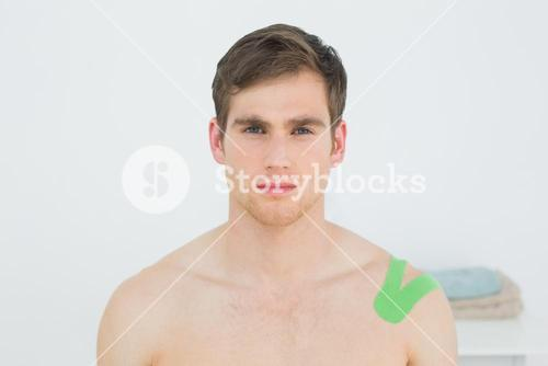 Handsome young man with green kinesio tape on shoulder