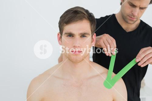Physiotherapist putting on kinesio tape on patients shoulder
