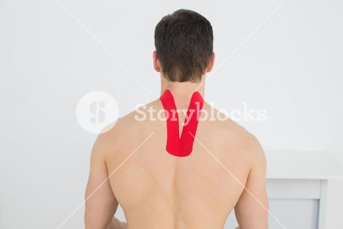 Rear view of a shirtless man with kinesio tape on back