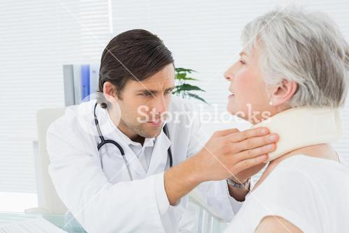 Male doctor examining a senior patients neck