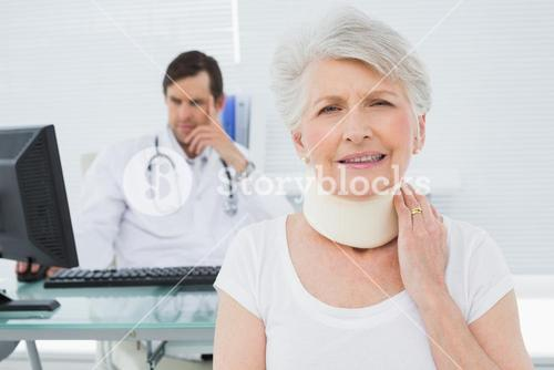Senior patient in surgical collar with doctor in background at office