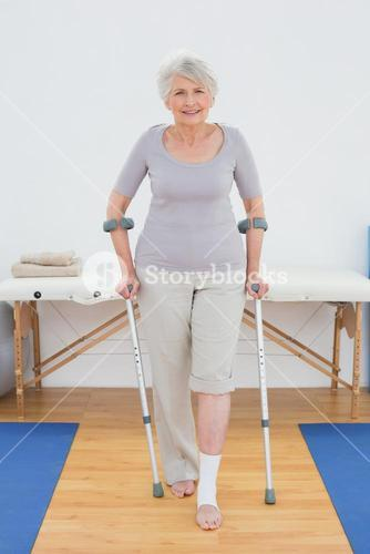Portrait of a smiling senior woman with crutches in hospital gym