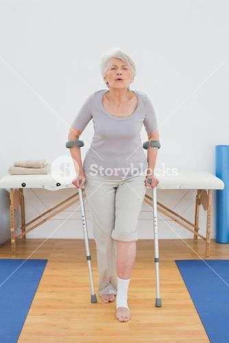 Full length of a senior woman with crutches in hospital gym