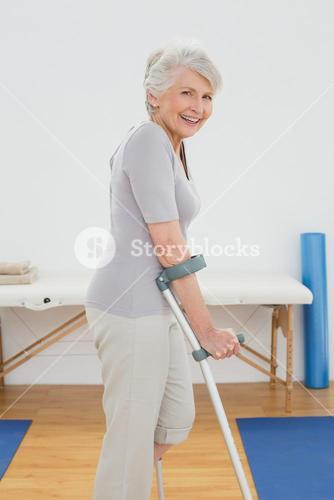 Side view of a smiling senior woman with crutches