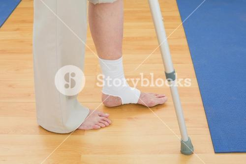 Low section of a woman with crutch and bandaged leg