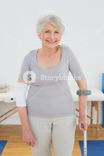 Portrait of a smiling senior woman with crutch