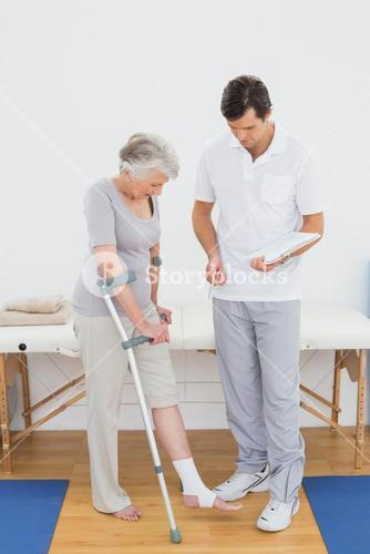 Male therapist examining disabled senior patient leg