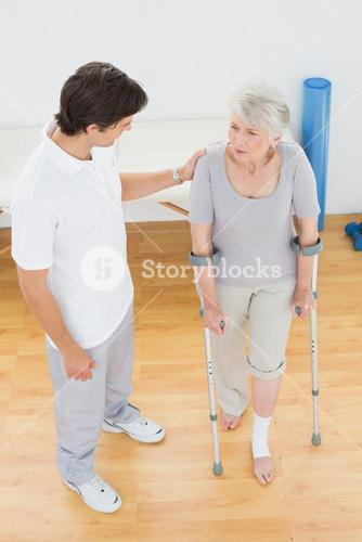 Male therapist in discussion with a disabled senior patient