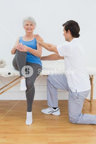 Male physiotherapist examining senior womans back
