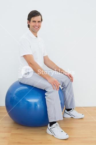 Smiling man sitting on exercise ball in hospital gym