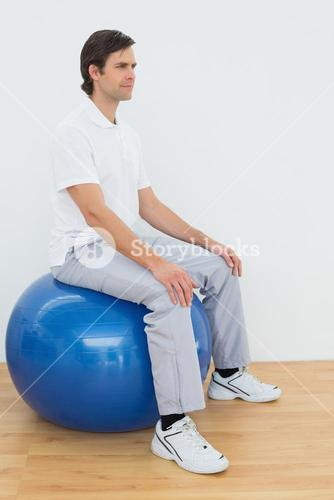 Young man sitting on exercise ball in hospital gym