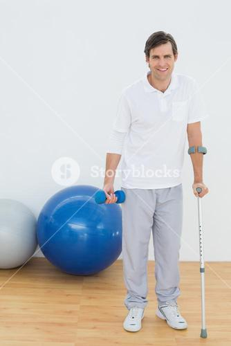 Portrait of a smiling man with crutch and dumbbell