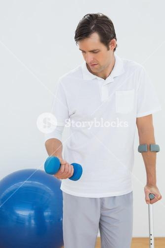 Young man with crutch and dumbbell
