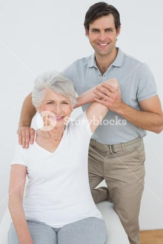 Physiotherapist stretching a smiling senior womans arm