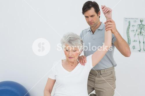 Male physiotherapist stretching a senior womans arm