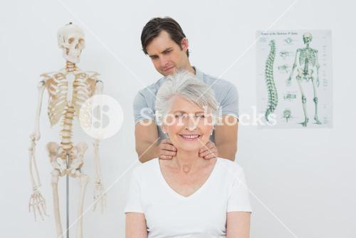 Male physiotherapist massaging a senior womans neck