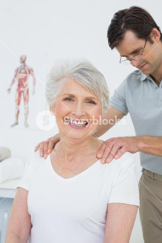 Male physiotherapist massaging a senior womans shoulders