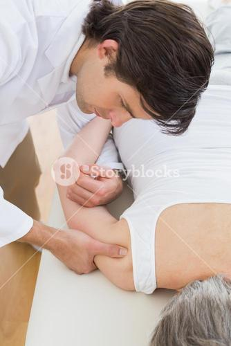 Physiotherapist massaging a senior womans arm