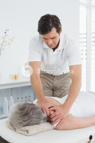 Physiotherapist massaging a senior womans shoulder