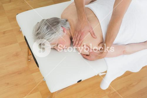 Physiotherapist massaging a senior womans back