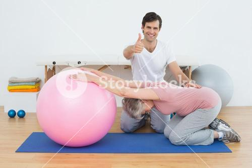 Therapist gesturing thumbs up by senior woman with yoga ball