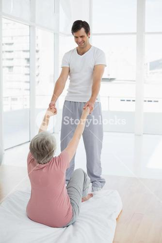 Therapist assisting senior woman with stretching exercises