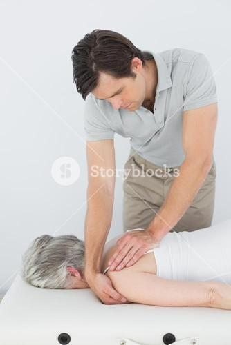Male physiotherapist massaging a senior womans shoulder