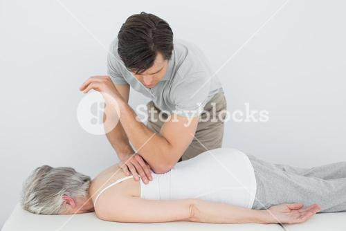 Male physiotherapist massaging a senior womans back