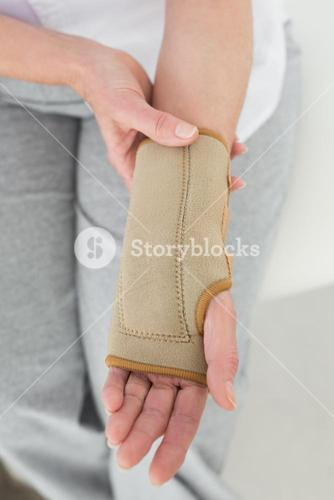 Closeup mid section of a woman with hand in wrist brace