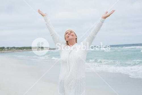Senior woman with arms outstretched at beach