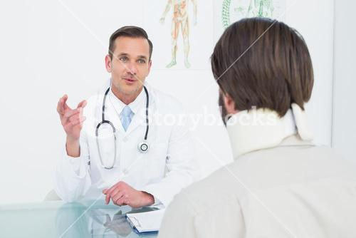 Male doctor in communication with patient at desk