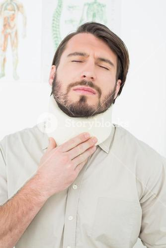 Young man suffering from neck pain with eyes closed