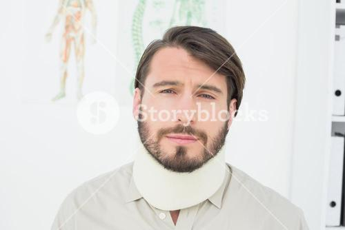 Portrait of a young man suffering from neck pain