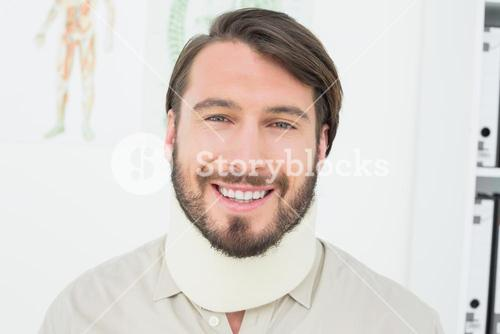 Portrait of a smiling young man wearing surgical collar