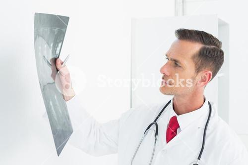 Concentrated male doctor examining xray