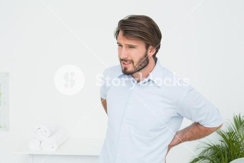 Handsome young man with back pain