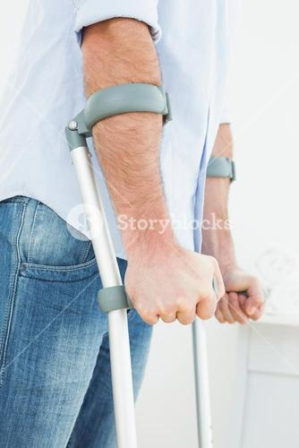 Closeup mid section of a young man with crutches
