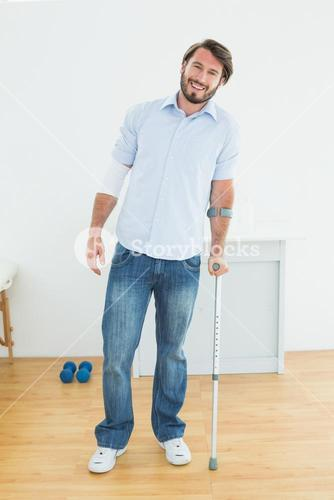 Full length portrait of a smiling man with crutch