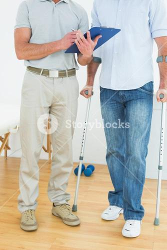 Therapist and disabled patient with reports