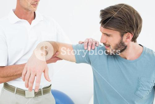 Male physiotherapist massaging a young mans arm