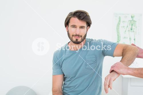 Male physiotherapist examining a young mans arm